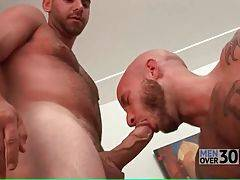 Bald bearded dude swallows fat cock of his tough friend.