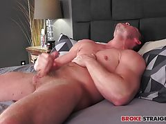 As he strips down, he shows us his sexy, built body, muscular and strong, and his amazing ass, before climbing onto the bed and grabbing his cock.  He lubes up his dick and starts to stroke it, getting hard in a matter of seconds as he pulls his shaft in