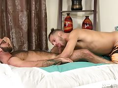 Fernando and Marco are sitting in their bed at the end of the day and Marco is obviously a little upset with Fernando. He feels neglected because Fernando has been working late a lot and they rarely have sex like they used to. Fernando tells him he is sor